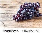 bunch of fresh black grapes on... | Shutterstock . vector #1162499272