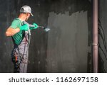 Building Elevation Pressure Washing by Worker with Power Washer. Refreshing House Outside Walls. - stock photo
