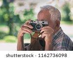 senior man taking photos with... | Shutterstock . vector #1162736098
