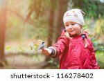 Adorable little girl and great tit bird sitting on her finger - stock photo