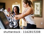 personal trainer helping woman... | Shutterstock . vector #1162815208