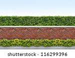 Shrubs And Brick Fence On Blue...