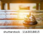 bell on the wood table in... | Shutterstock . vector #1163018815