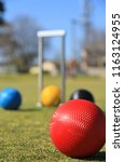 Small photo of In the foreground is a red croquet ball on a green croquet lawn in Australia with a defocused croquet hoop and balls in the background
