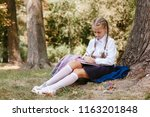 a schoolgirl does lessons in a... | Shutterstock . vector #1163201848