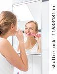 pretty female brushing her... | Shutterstock . vector #1163348155