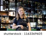 Small photo of The waitress takes the customer's order in the hotel restaurant. Morning time. The girl is smiling. A barmaid woman takes an order holding the tray by hand of the hotel bar. The concept of service.