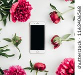Small photo of WARSAW / POLAND - AUGUST 20, 2018: iPhone 8 Plus by Apple in frame of pink peonies flowers on white background. Flat lay, top view mock up.