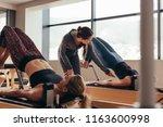 two fitness women doing pilates ... | Shutterstock . vector #1163600998