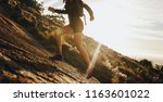 woman running up a rocky... | Shutterstock . vector #1163601022