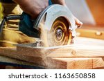 Building contractor worker using hand held worm drive circular saw to cut boards on a new home constructiion project - stock photo