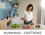 woman preparing salad in the... | Shutterstock . vector #1163726362