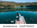 young woman sitting on peer and ... | Shutterstock . vector #1163733415