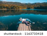 two friends resting on peer and ... | Shutterstock . vector #1163733418