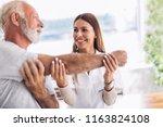 man having chiropractic arm... | Shutterstock . vector #1163824108