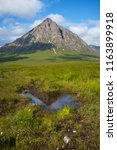 Reflection of Buachaille Etive Mor in a puddle on a meadow near Kings house on West Highland Way in Scotland