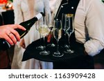 waiter pouring some champagne... | Shutterstock . vector #1163909428