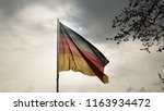 Small photo of The German National Flag in front of a grey cloudy Sky.