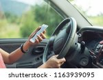 women driver with a cell phone... | Shutterstock . vector #1163939095
