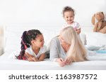female mature nanny with little ... | Shutterstock . vector #1163987572