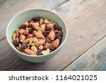 mix nuts in bowl on wooden... | Shutterstock . vector #1164021025