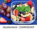 fresh fruit salad on blue... | Shutterstock . vector #1164026365