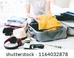 woman packing travel bag for... | Shutterstock . vector #1164032878