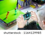 Small photo of KROPIVNITSKIY, UKRAINE – 12 MAY, 2018: Stop motion animation process with Stikbot details and toy figures. Boy expose stop motion elements to create animations using smartphone