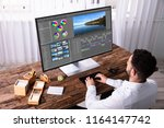 young male editor editing video ... | Shutterstock . vector #1164147742