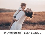 young woman kisses her little... | Shutterstock . vector #1164163072