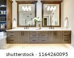 Master bathroom interior in luxury modern home with dark hardwood cabinets, white tub and glass door shower