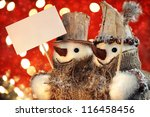 Snowmen holding blank sign against a red christmas background - stock photo