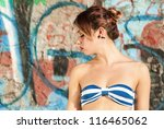 thoughtful woman portrait with a wall on background - stock photo