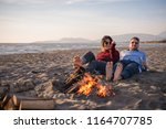 young couple relaxing by the... | Shutterstock . vector #1164707785