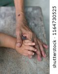 the hand of the little boy is... | Shutterstock . vector #1164730525