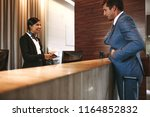 businessman check in at hotel...   Shutterstock . vector #1164852832