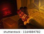 couple sitting in woolen socks... | Shutterstock . vector #1164884782