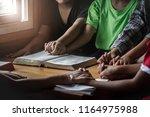 children group praying together ... | Shutterstock . vector #1164975988