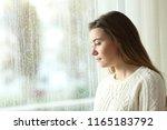 sad woman looking outdoors... | Shutterstock . vector #1165183792