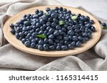 plate with ripe blueberries on... | Shutterstock . vector #1165314415