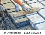 a workman's gloved hands use a... | Shutterstock . vector #1165336285