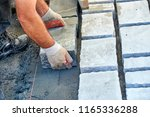 a workman's gloved hands use a... | Shutterstock . vector #1165336288