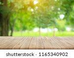 wood floor with blurred trees...   Shutterstock . vector #1165340902