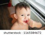 cute little boy eating... | Shutterstock . vector #1165384672