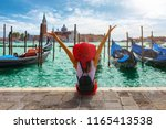Small photo of Happy traveller woman sits in front of the traditional gondolas of St. Mark's Square in Venice, Italy