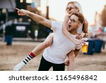 young couple piggy backing at... | Shutterstock . vector #1165496842