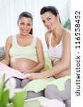 Two young future pregnant women preparing baby clothes together - stock photo