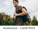 man hiking in a countryside... | Shutterstock . vector #1165679425