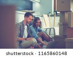 young couple moving in new home.... | Shutterstock . vector #1165860148
