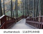 Long wooden staircase in the autumn forest Park, top-down view of the bare trees